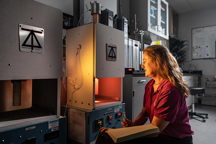 Image of APL planetary scientist Nancy Chabot at a furnace in APL's Meteorite Laboratory